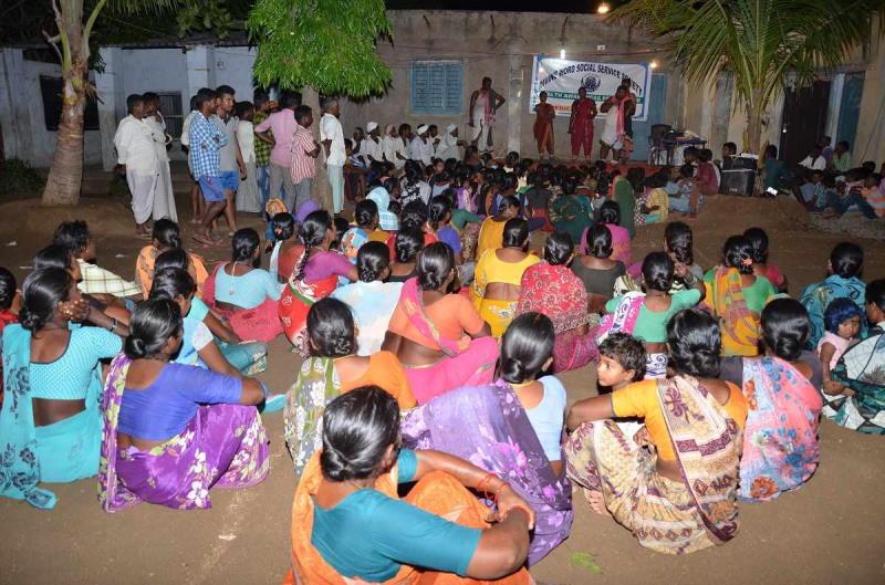 Frauen und Kinder sitzen abends in einem Hof und sehen einer Show zur Aufklärung über Hygiene während eines Gesundheitscamps zu.