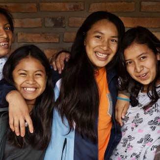 Drei Mädchen aus Bolivien lächeln in die Kamera