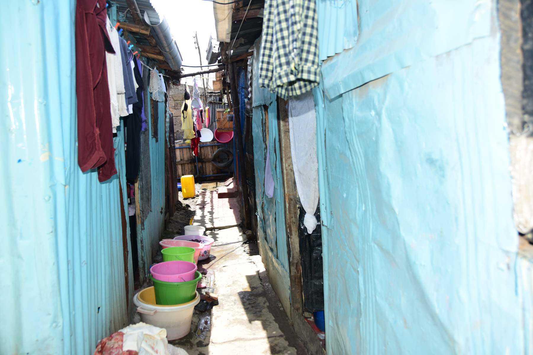 Eine enge Gasse mit zum Trocknen aufgehängter Wäsche und Wascheimern in einem Slum in Nairobi.