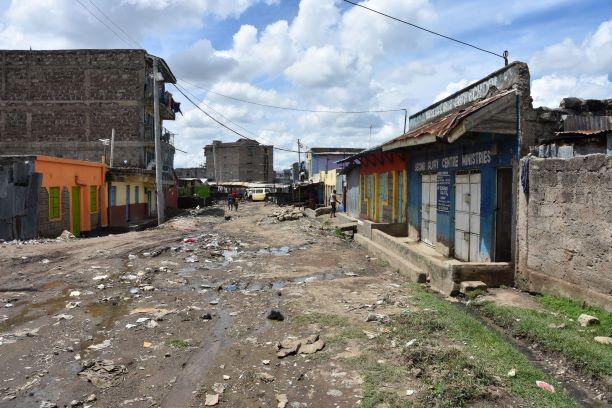 Eine menschenleere unasphaltierte Straße in einem Slum in Nairobi.