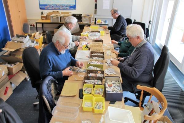 Mitarbeiter des Briefmarkenapostolats beim Schneiden und Sortieren von Briefmarken.
