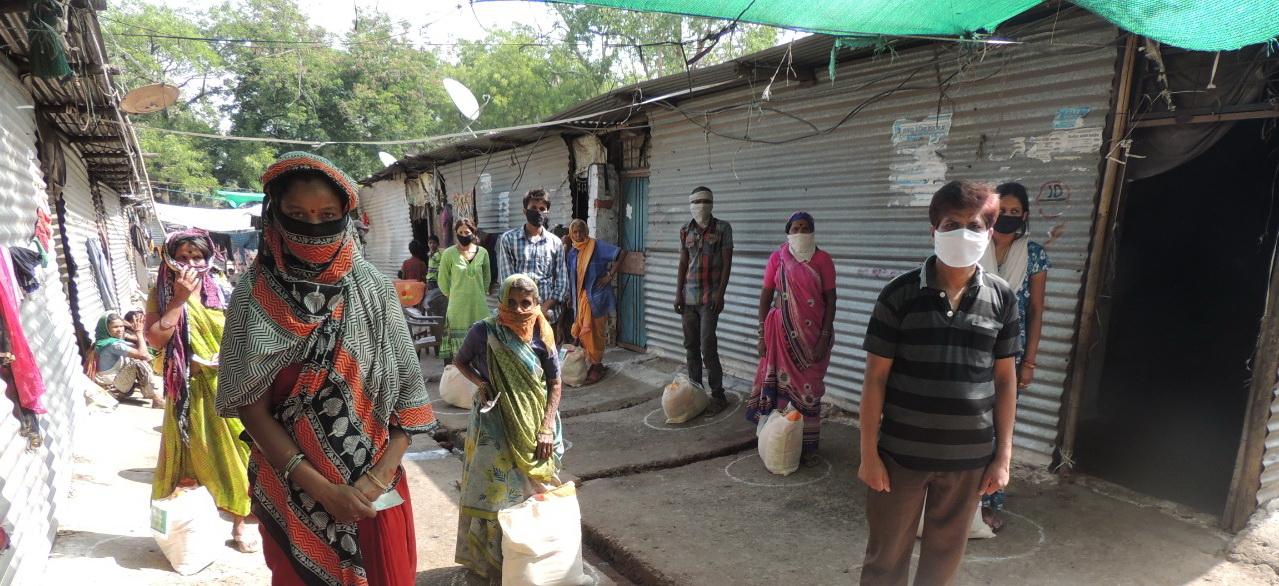 BewohnerInnen von einem Slum in Indien reihen sich auf für die Verteilung von Corona-Nothilfe-Paketen.
