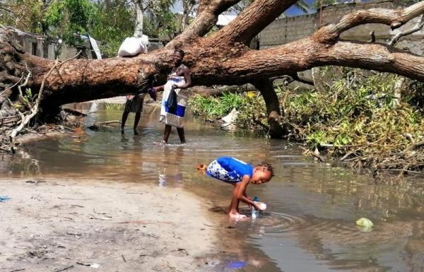 Ein Kind spielt im Wasser nach einer Überschwemmung in Mozambique. Im Hiintergrund ist ein umgefallener Baum. Eine Frau sieht dem Kind zu.